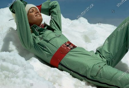 Model reclined in the snow wears green ski overalls by Liberty Bell with a red belt at waist.