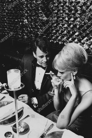 In the room of the ceiling of lights at The Ground Floor in the Saarinen-designed CBS skyscraper, a dark man in a plush dinner suit by LeBaron of blue wool and velvet with a diamond pattern woven on the jacket leans toward a blond woman in a shimmering dress, drinking, and holding a cigarette.