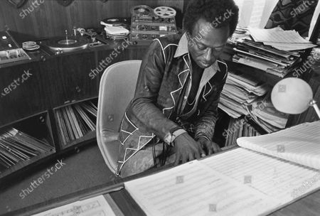 Musician Miles Davis composing at keyboard wears a long-sleeved, reversed suede vest in a room filled with recording equipment and vinyl records. Miles Davis