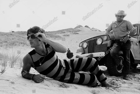 A male model lounging on a beach in front of a jeep and a police officer wearing a pair of aviator sun glasses, striped tank-suit with a high scoop neck made of ribbed acrylic fiber by Drummond.