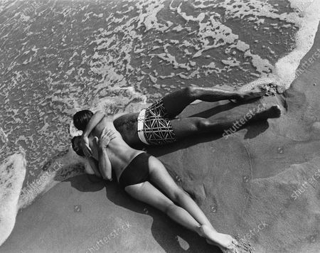 Two models on a beach in the surf; the woman in a black bathing suit bottom on top of a male model in a red-on-blue Union Jack-inspired motif boxer swimming trunks with matching white webbed belt by Oleg Cassini for Sea Mark.