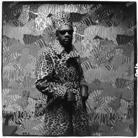 Stock Photo of Soul singer Isaac Hayes wearing a belted leopard print trench coat and matching turban. Isaac Hayes