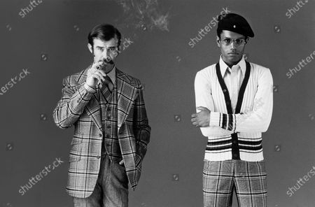 Portrait of two men: Left (Caucasian) model wears a plaid jacket and vest with tweed pants all by Cricketeer, a collared shirt by Bert Pulitzer and a Pierre Balman tie while smoking a cigarette; Right (African-American) model wears a Van Heusen cardigan, Tattersall shirt by Byron Britton for Aetna and Cricketeer plaid pants with aviator sun-glasses and a beret.