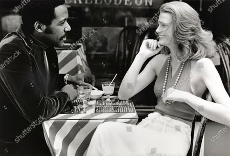 Actor Richard Roundtree seated with model at an outdoor cafe; Model wearing a wrapped halter by White Stag over drawstring-top pants by Mr. Pants Inc.