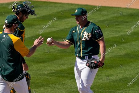 Oakland Athletics pitcher J.B. Wendelken is pulled from the game by manager Bob Melvin, left, during the fourth inning of a spring training baseball game against the Chicago Cubs, in Mesa, Ariz