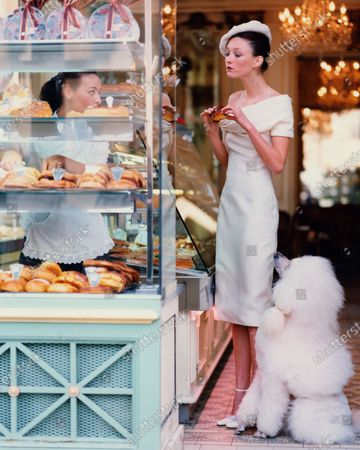 Model Audrey Marnay holding a pastry and standing at the counter at the Pâtisserie Cador, Paris with a Standard Poodle at her feet and a salesperson behind the counter. Marnay is wearing a cream linen side-buttoned day dress with an asymmetrically knotted collar by Christian Dior Haute Couture in fabric by Bellora, cream beret by Stephen Jones with Christian Dior Atelier and cream high-heeled shoes by Manolo Blahnik. Audrey Marnay