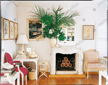 The library of Hibiscus Hill, the home of India Hicks and David Flint Wood on Harbour Island, Bahamas featuring a fireplace decorated with palm leaves from the garden, a small canvas chair labeled with their son's name Felix to the left of the fireplace and framed art on the walls.