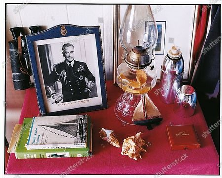 A bedside table in Hibiscus Hill, the home of India Hicks and David Flint Wood on Harbour Islands, Bahamas with books, shells, glass lantern and a framed photograph of Lord Mountbatten of Burma, the last Viceroy of India and HIcks' grandfather. Louis Mountbatten, 1st Earl Mountbatten of Burma
