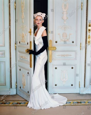 Model Audrey Marnay standing in a doorway at the Hôtel Ritz, Paris and wearing a long, mermaid-line cream crepe evening dress flaring into pleats with asymmetrical overstitching and long black gloves, both by Christian Dior Haute Couture with a white pig mask by Stephen Jones with Christian Dior Atelier; dress fabric by Bianchini. Audrey Marnay