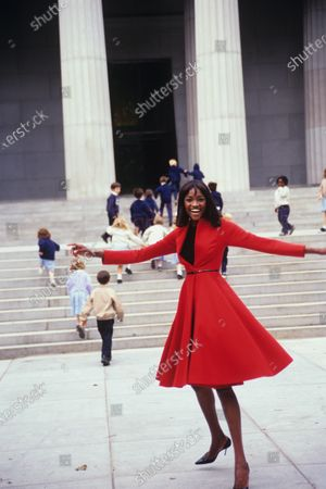 Stock Image of Model Oluchi Onweagba spinning her belted crimson swing coat by Donna Karan, in front of children running up steps. Oluchi Onweagba