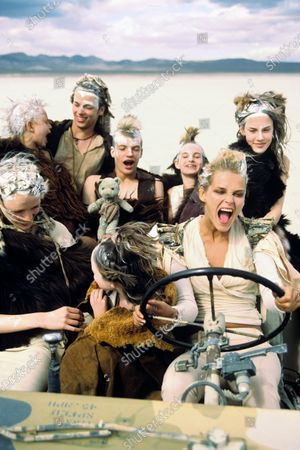 Madly Max model Carmen Kass driving children-filled jeep, wearing beige wrap top with shoulder pads and skinny pants by Nicholas Ghesquiere for Balenciaga LeDix. Carmen Kass