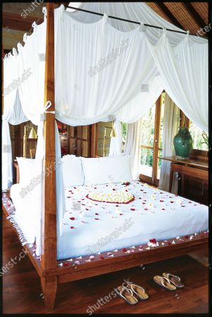 A canopied honeymoon bed decorated with rose-petal heart at Bali's Begawan Giri Estate.