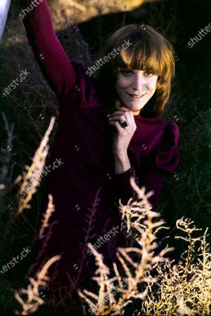 American actress, Carrie Snodgress wearing a burgundy dress sitting amongst tall grass. Carrie Snodgress