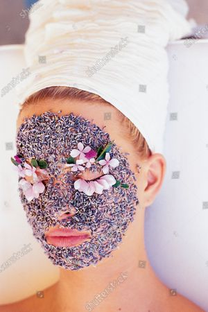 Head shot of model Karolina Kurkova with her face coated in lavender and flower petals for eyebrows and eyelashes; Taken at the spa La Ferme Thermal, one of the four hotels/spas of Les Près d'Eugènie, owned and operated by Michel and Christine Guérard, in the Landes region of France. Karolina Kurkova