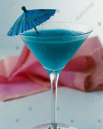 A Blue Hawaiian cocktail served in a martini glass with a blue cocktail umbrella on the left side of the drink.