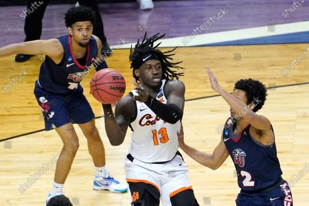 Oklahoma State guard Isaac Likekele (13) passes under pressure from Liberty's Darius McGhee (2) as Chris Parker watches during the first half of a first round NCAA college basketball game, at the Indiana Farmers Coliseum in Indianapolis