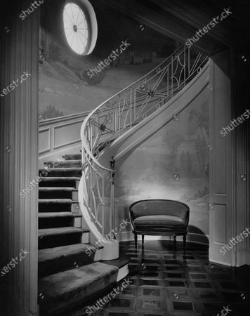 Interior, broad curving stair with round window to light in top left, mural on walls, cushioned seat at foot of stairs; home of W. E. Shepard.