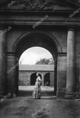 Dr. Edith Sitwell; English poet and socialite and daughter of Sir George Sitwell; at age sixty-one, stands outside in front of a concrete arch and columns; she wears a Renaissance inspired dress made of floral fabric; she is photographed in profile with her hands on her hips.