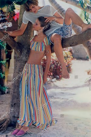 Female model wearing matching striped short top and shirred long skirt by Loomtogs of Dacron and cotton by Folker Fabrics, standing next to tree on which a male model sits.