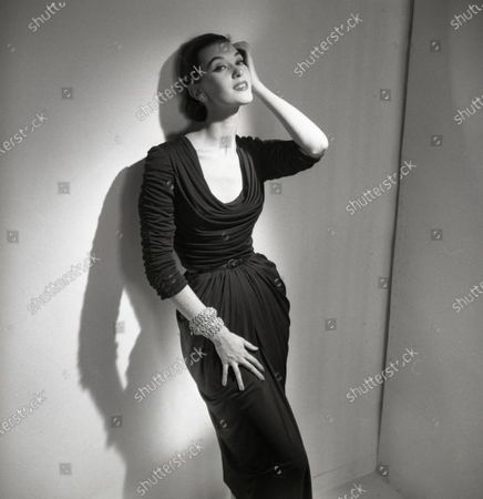 Model Barbara Mullen poses, leaning against wall, combing hand through hair; she wears a fitted and draped dress of mat jersey with cowl collar by Talmack with jewelry by Fashioncraft; hair pulled back. Barbara Mullen
