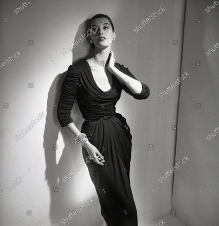 Model Barbara Mullen poses against wall, one hand on hip, the other at neck; she wears a fitted and draped mat jersey dress with cowl collar by Talmack and jewelry by Fashioncraft; hair pulled back. Barbara Mullen