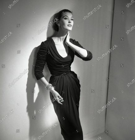 Model Barbara Mullen poses with back against wall, left hand at neck; she wears a fitted and draped mat jersey dress with cowl collar by Talmack and jewelry by Fashioncraft; hair is pulled back. Barbara Mullen