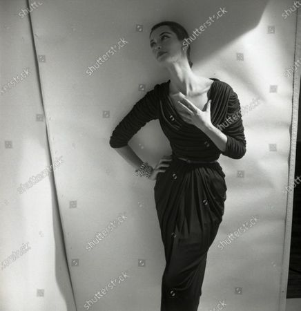 Model Barbara Mullen leans against wall, one hand is at hip, the other at neck; she wears a fitted and draped mat jersey dress with cowl collar by Talmack and jewelry by Fashioncraft; hair is pulled back. Barbara Mullen