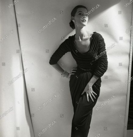 Model Barbara Mullen poses, leaning against wall; she wears a fitted and draped mat jersey dress with cowl collar by Talmack and jewelry by Fashioncraft; hair is pulled back. Barbara Mullen