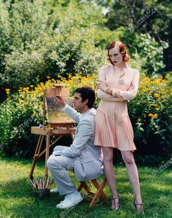 Redhead model, Karen Elson, wearing pleated peach silk dress by Nicholas Ghesquiere for Balenciaga, standing arms-crossed next to model, Johnny Zander, painting at an easel. Karen Elson, Johnny Zander
