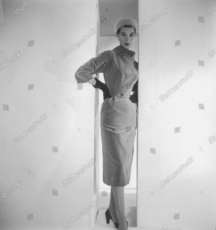 Model Barbara Mullen  stands in doorway with hands on hips; she wears a velvet dress for day and cocktails with an oversize turtleneck collar; gloves, and an Angora hat; dress by Adele Simpson; hat by Mr. John. Barbara Mullen