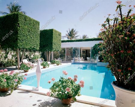 The pool and gardens at the Palm Beach, Florida, vacation home of Enid A. Haupt, editor and publisher of Seventeen magazine. On the left are two large ficus trees which have been pruned into squares. Between two potted geraniums is a marble sculpture by Signori. On the right is a crown of thorns in full bloom. On the roof over the dining loggia, a hedge of ficus grows in a trough; the dining area is visible through the sliding glass doors.