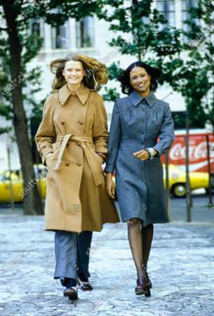 The model on the left is wearing a camel trench coat by Emmanuelle Khanh, gray striped wool pants by Franck Olivier, taupe and brown pumps by Levant Footwear; on the right, model Beverly Johnson is wearing a gray wool shirtdress-like coat by Lassie Junior, shoes by Sergio Rossi , Round-the-Clock stockings, silver bracelets by Alexis Kirk. Beverly Johnson