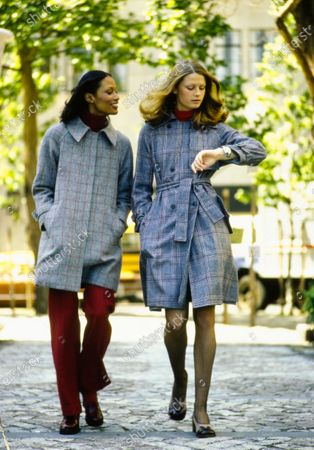 On the left, model Beverly Johnson is wearing a gray wool coat with red stripes, a fly-front and raglan sleeves, red pants and a red turtleneck sweater, all by Daniel Hechter shoes by Casadei by Carber; the model on the right is checking her watch while wearing a gray wool plaid trench coat by Pierre d'Alby, the taupe and brown pumps are by Levant Footwear, Belle Sharmeer stockings and a red Sant' Angelo for Allstate turtleneck bodysuit. Beverly Johnson