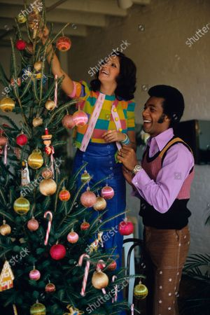 Diana Seijo and singer/actor Clifton Davis decorating a Christmas tree. Ms. Seijo is wearing a checked sweater set and blue button-up corduroy pants, all by Betsey Johnson for Alley Cat. Mr. Davis is wearing a pink button-down shirt beneath an orange, pink and black sweater vest and brown pants with white stars.