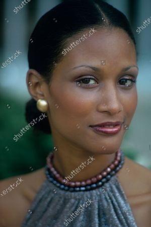 A headshot of model Beverly Johnson. The shiny halter top of a dress by Barbara Groot for Craig is visible as well as plum and black pearl necklaces. Beverly Johnson