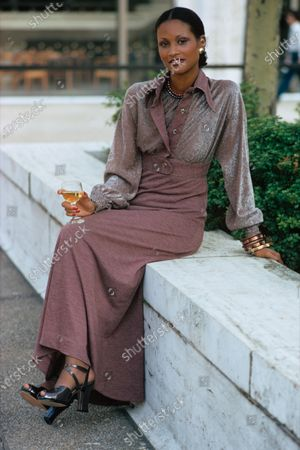 Stock Image of Model Beverly Johnson sitting on a concrete wall, wearing a long heathered plum dress with a short, shimmering jacket with matching trim by Barbara Groot for Craig. Ms. Johnson's hair is pulled off of her face. She is holding a glass of white wine. Beverly Johnson