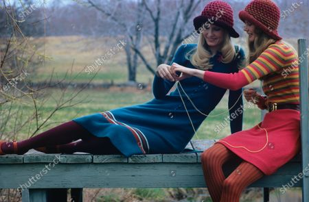 Two models sitting on a bench sharing a piece of yarn. The model on the left is wearing a blue sweater dress with red and white stripes on the hem by Rosanna, maroon knit hat by Veaumont, stockings by Beauty Mist, and red shoes by Mr. Seymour. The model on the right is wearing a dress that is red, yellow, and green striped on the top and solid red on the bottom, by Pat Ashley for Craig. She is also wearing a red knit hat by Veaumont, copper stockings by Danskin, brown belt by Benson and Partners.