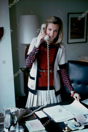 Linda Buck, an anti-trust lawyer for Gulf Oil Corp., stands at her desk holding white telephone receiver to right ear with her left hand on notebook pages; she wears a Liz Claiborne for Youth Guild outfit of blended fibers: white pleated skirt, short-sleeved knit jacket over a dark red sweater, long-sleeved print shirt of Dacron by Klopman and three Kenneth Jay Lane bangle bracelets; her hair is styled by James Reda. Linda Buck