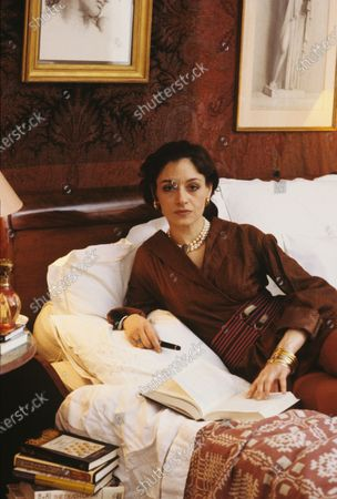 Author Joan Juliet Buck reclines in her New York bedroom, with an open book, wearing her grandmother's pearls. Joan Juliet Buck