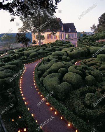 The winding path, highlighted by thousands of candles and clipped boxwood plants leads to the Chateau de Marqueyssac.