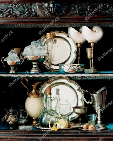 Stock Photo of A 16th century buffet includes some Louis XVI sterling silver plates, Puiforcat bowls, nautilus shells mounted on candlesticks designed by Coorengel and Calvagrac, a ostrich eggshell and gilt silver carafe and glassware.