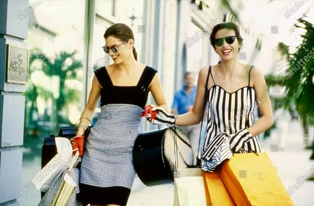 Models Carre Otis and Fabienne Terwinghe walking along famed shopping street, Worth Avenue in Palm Beach, Florida, both carrying many shopping bags. Otis, left, wears Carolina Herrera's black-and-white checked linen sundress, sunglasses by Morgenthal-Frederics, red gloves from Paloma Picasso, gold bag by Carlos Falchi, and a navy bag from Susan Bennis Warren Edwards for Carolina Herrera. Terwinghe, right, wears a black-and-white striped cotton jersey dress and carries the matching jacket, both from Geoffrey Beene. Styled with sunglasses by Christian Roth for Optical Affairs and Geoffrey Beene striped gloves to match the dress. Hair by Mitch Barry. Makeup by Sonia Kashuk. Carre Otis, Fabienne Terwinghe