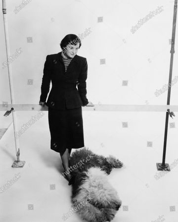 Designer Florence Knoll and her dog posing for a photo.