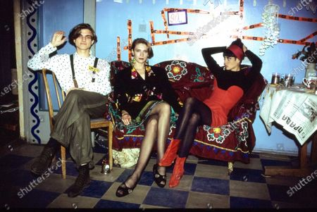 Designer Konstantin Goncharov (left), model and actor Irina Kuksenaite (center), and model Christy Turlington (right) on a couch draped in cloth embroidered with traditional Russian floral motifs in the St. Petersburg apartment of Russian artist Afrika (also husband of Irina Kuksenaite).Christy Turlington wears a strapless red dress over a black turtleneck by Yohji Yamamoto, with a red headband by Eric Javits and red boots by Manolo Blahnik.Konstantin Goncharov wears a white shirt with black polka dots and loose olive green pants with suspenders. Irina Kuksenaite wears a black short dress trimmed in geometrically-patterned cloth. Konstantin Goncharov, Irina Kuksenaite, Christy Turlington