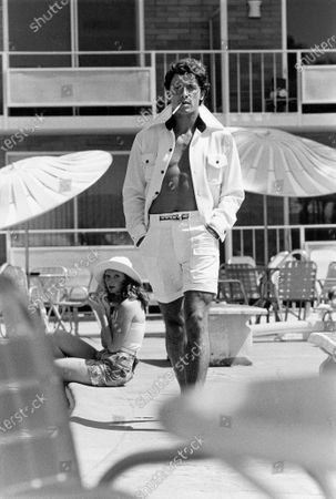 Shirtless man smoking a cigarette, wearing sunglasses, a white knit jacket by Jump Suits Ltd. and white shorts by Rough Rider; his ribbon stripe belt is by Mr. R; a woman sitting with her feet in a pool and applying lipstick is in the background.