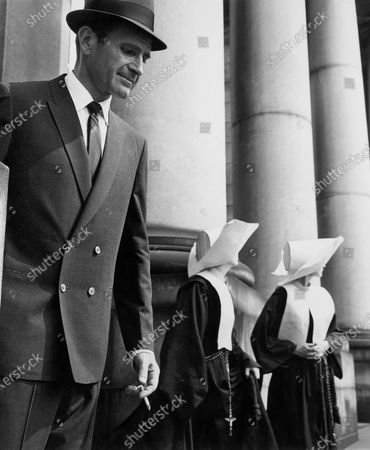 Man standing in front of large columns, wearing a dark double-breasted suit and fedora, holding a cigarette and looking down; there are two nuns to the right of him.
