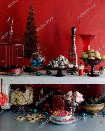 A display of holiday cookies, containers, a bird cage, ornaments and a holiday tree.