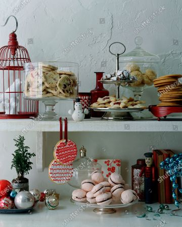 A display holiday cookies, containers, ornaments and a bird cage.
