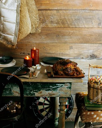 Braised pork shoulder on a platter, sitting on a wooden table; also on the table are plates, candles and silverware; a fur lined jacket hangs on hook above table while a dart board is placed on the floor under the table; a bucket of colored pencils sits on a chair to the right of the table.