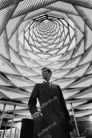 Male model posing in the Man in the Community Pavilion at Expo 67 wearing a four buttoned DB hound's-tooth checked blazer with square shoulders, peak lapels, straight flap pockets and deep side vents, by Hammonton Park.